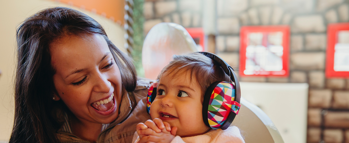 Mother with daughter wearing headphones